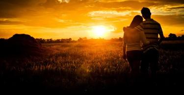 Zaljubljeni par gleda zagrljen prema zalasku sunca
